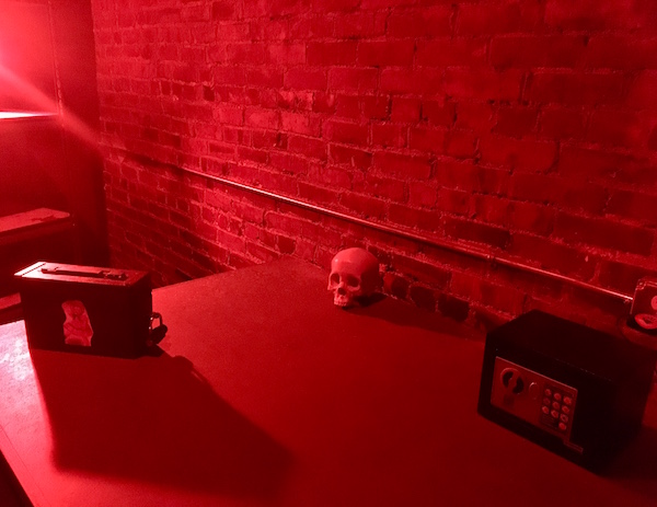 In-game: a large red lit table with a small sage, a skull, and a locked ammo box.