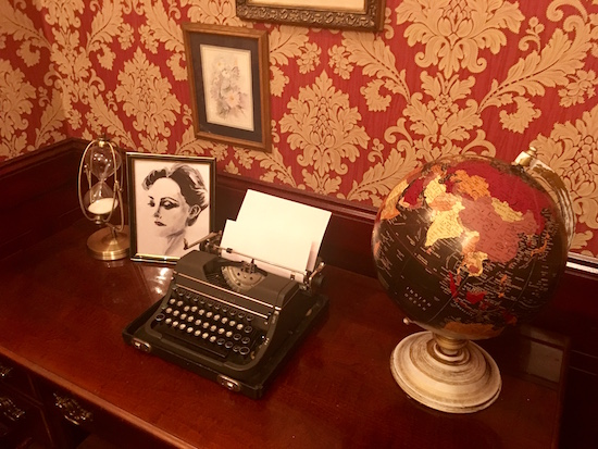 In-game: a desk with a typewriter, globe, hour glass, and photo of a beautiful woman.
