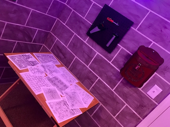 In-game: a drafting table with toy designs, mounted to the wall above are toy tools.