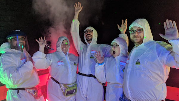 Our team in white onesies with our hands in the air.