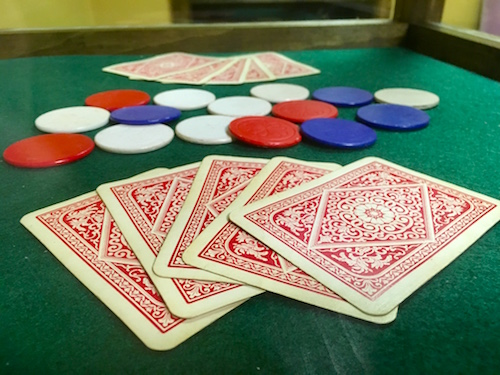 In-game: two face down hands of cards and some chips on a card table.