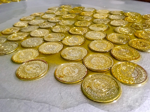 In-game: a collection of gold coins lacquered to a silver table. The lacquer is clearly pooled around the coins.