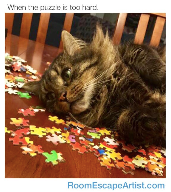 """When the puzzle is too hard."" A cat with an exhausted look laying atop a pile of jigsaw puzzle pieces."