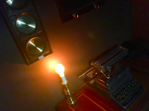 In-game: A typewriter beside an exposed glowing lightbulb in an otherwise dim room.