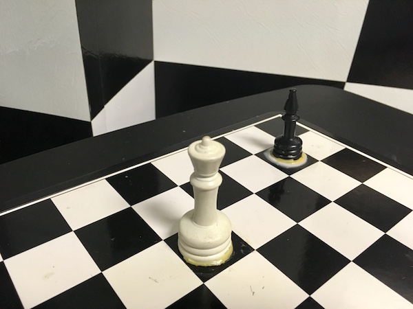 In-game: A chess set with a black bishop and white queen affixed to the board.