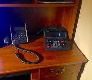 In-game: A telephone and calculator on a desk.