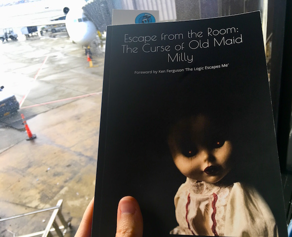 Escape from the Room: The Curse of Old Maid Milly being held up beside an airport window.