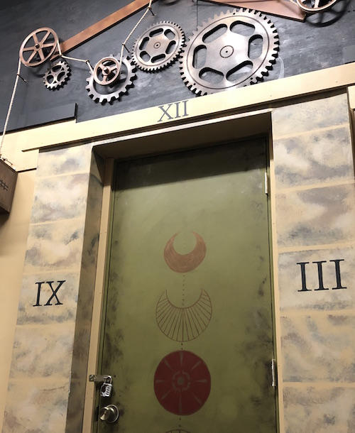 In-game: A door with moon cycles painted on it, a clock face around it, and large gears above.