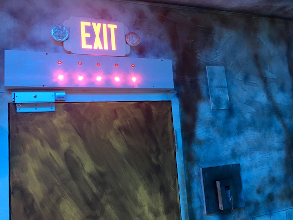 In-game: An exit door with 5 glowing lights above it.