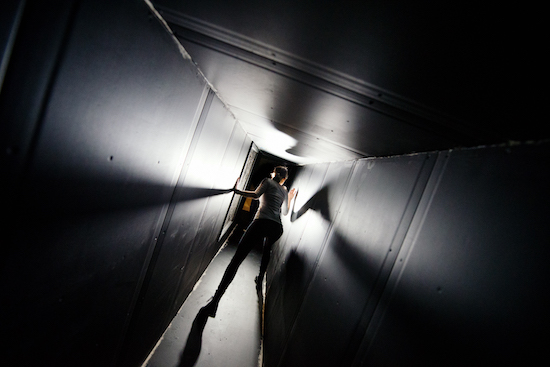 A woman crouched and walking cautiously through a dark vent or tunnel.