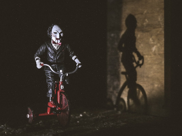 Jigsaw from Saw sitting on a tricycle.