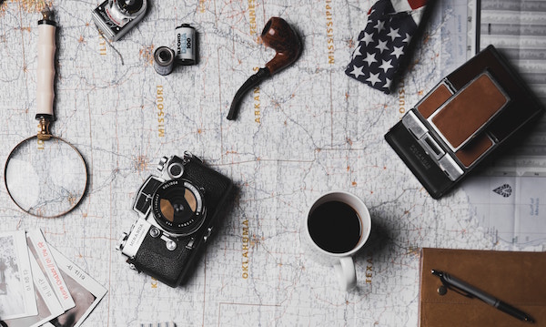 A map covered in assorted items like a camera coffee cup, notebook, pen film, American flag.