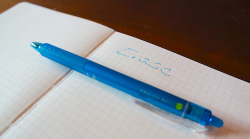 "Blue FriXion pen on graph paper, beside the word, ""Erase"" with a line erased down the middle of the word."