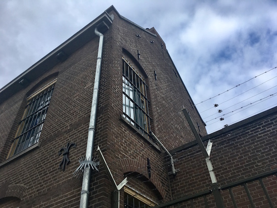 Exterior of the Breda Prison Dome with barred windows and barbed wire.