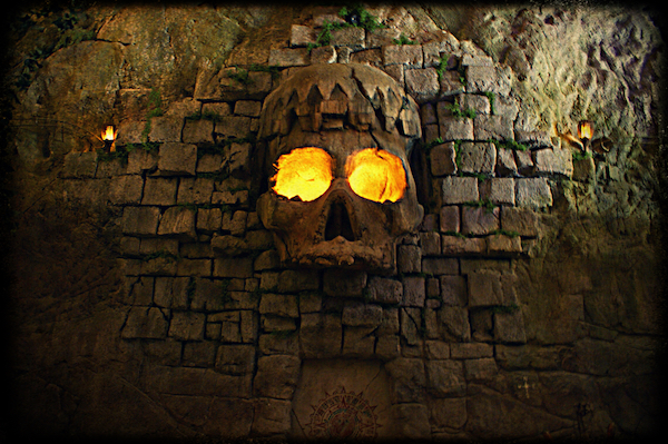In-game: a large stone wall with a massive skull carved into it. The skull's eyes glow with fire.