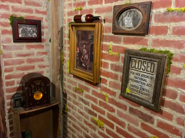 In-game: A corner of the brick wine cellar with a few photos, a bottle of wine, and an old radio.