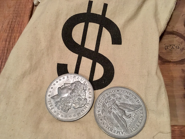 In-game: Close-up of a money back and large silver dollars.