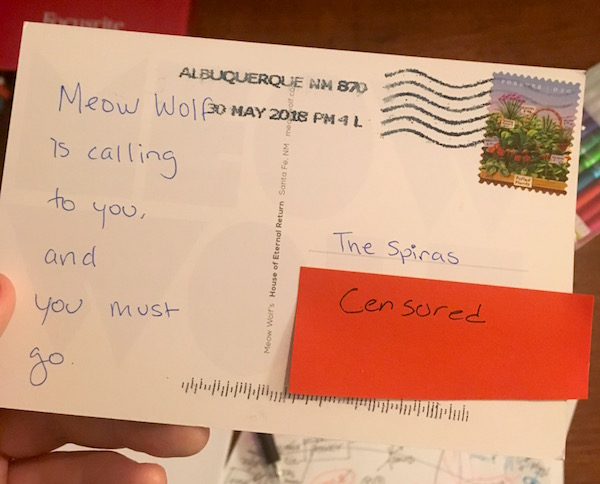 "A postcard addressed to ""The Spiras"" reads, ""Meow Wolf is calling to you and you must go."" No signature."