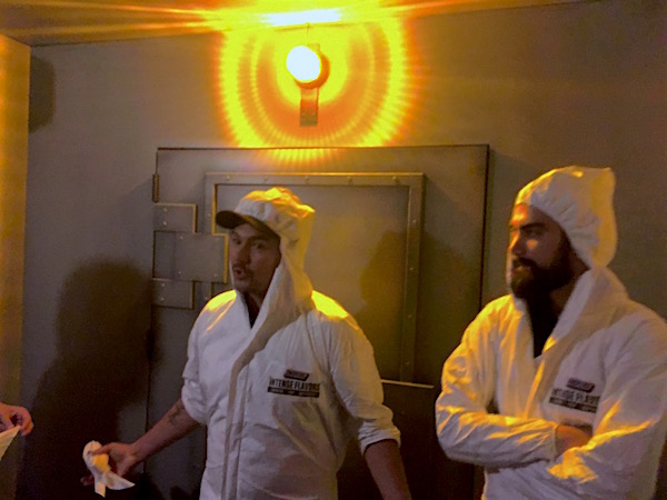 In-game - Two gamemasters in white jumpsuits in front of the bunker door.