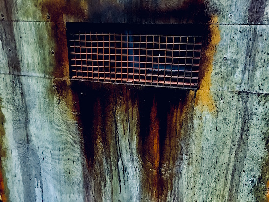 In-game: a closeup of a cell door with a rusty grate.