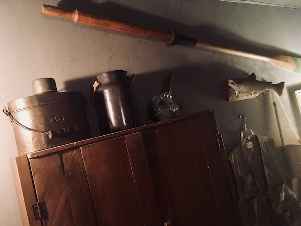 In-game: A cabinet ore, and taxidermied fish hanging on the wall of a fishing cabin.