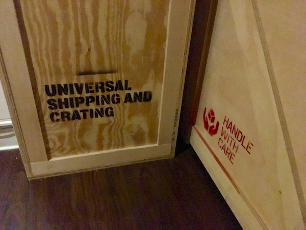 "In-game: closeup of two crates, one labeled, ""Universal Shipping and Crating,"" the other, ""Handle with care."""