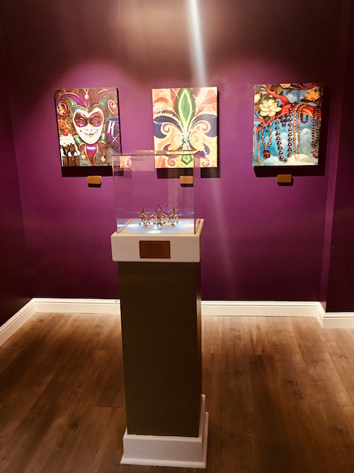 In-game: A purple walled art gallery with Mardi Gras paintings hung from the walls. In the middle of the room encased in glass is a crown on a pedestal.