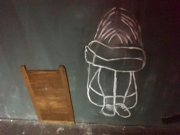 In-game: A small wooden door against a black wall with a chalk drawing of a young girl curled up seemingly crying.