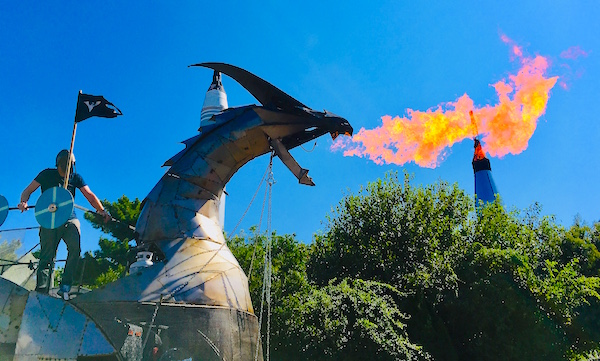 A man standing on a giant mechanic firebreathing dragon at Maker Faire NY