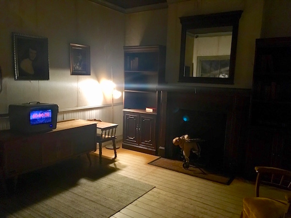 In-game: the grim livingroom of an old rundown home.