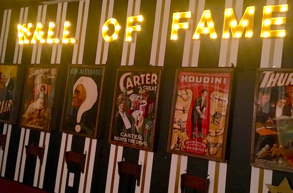 In-game: a magician wall of fame featuring posters of some of history's move famous illusionists.