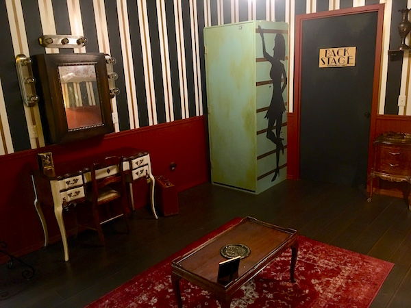 In-game: a wide shot of a large portion of the dressing room set. There is a large box with the silhouette of a woman painted on it.