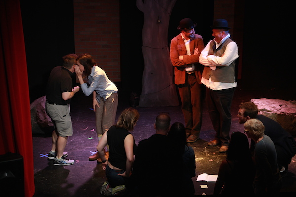 Two actors standing on stage while another actor whispers to a player