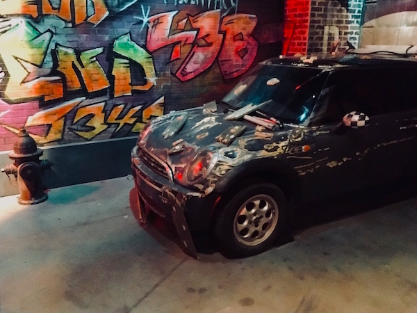 In-game: a Mini Cooper that crashed through a garage in front of a graffitied wall.