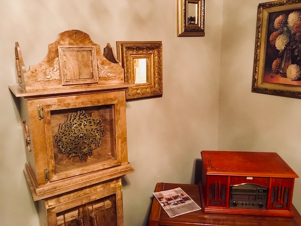 In-game: an old record player beside a strange and ornate wooden grandfather clock.