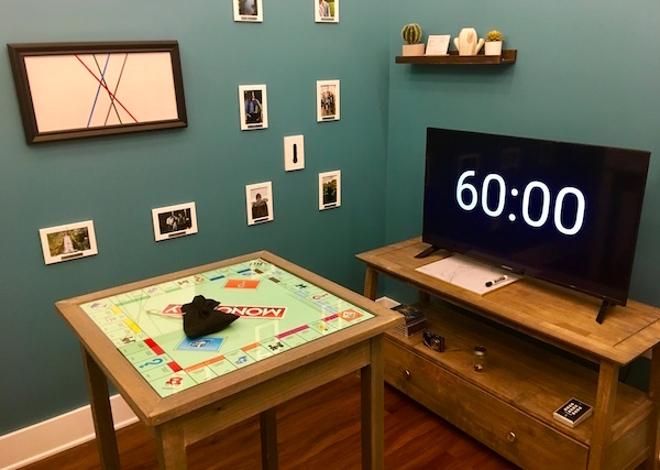In-game: Apartment A features a TV displays a 60 minute clock, a small table with a Monopoly board, and a wall of photos and cacti.
