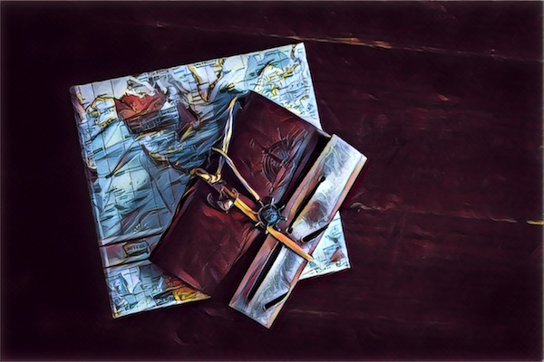 An ornate leather wrapped notebook resting on a map.