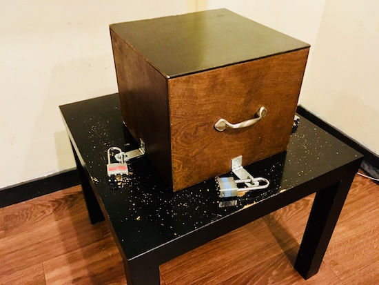 In-game: a wooden box locked down to a very beat up table by three padlocks.