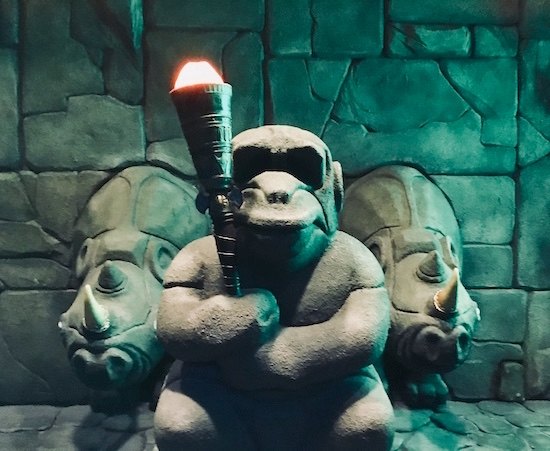 In-game: a monkey statue holding a torch flanked by two rhino statues.