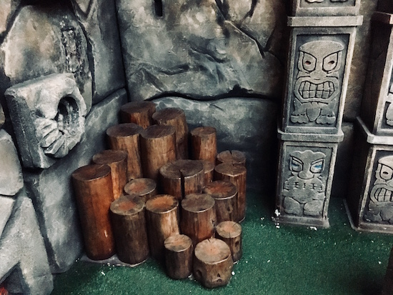 In-game: stone walls and pillars beside a collection of tree stumps.