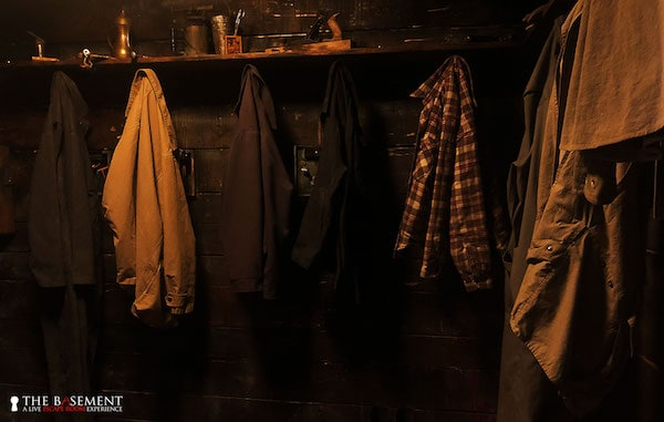 In-game: Coats hanging in a dim, creepy mud room.