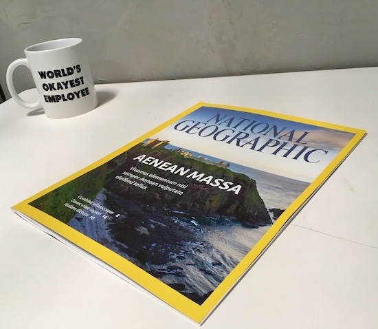 "In-game: a desk with a National Geographic magazine beside a coffee mug that reads, ""World's Okayest Employee."""