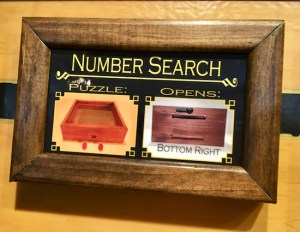 "In-game: a framed puzzle description labeled ""Number Search."" It shows the puzzle component and the box that it opens."
