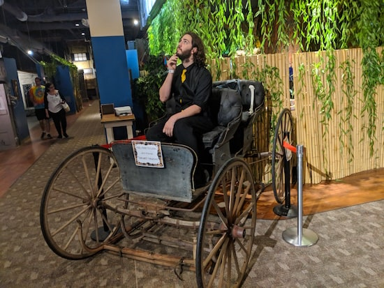A Museum of Intrigue character posing in an antique carriage.