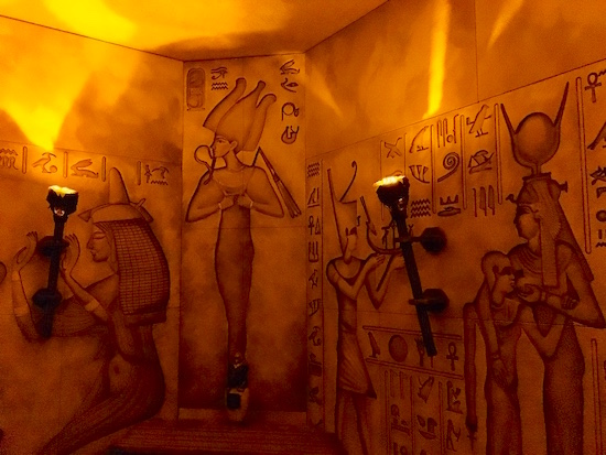 In-game: the torch-lit walls of an Egyptian tomb with carvings and hieroglyphics.