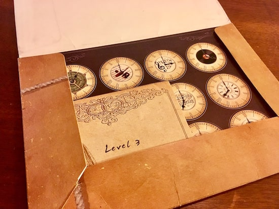 "In-game: A folder with a piece of paper with a matrix of clock faces, and an envelope labeled, ""Level 3."""
