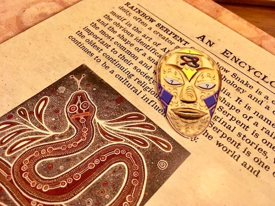 In-game: A colorful Aboriginal mask over a text about the myth of the Rainbow Serpent.