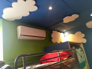 In-game: Nicolai's bunk bed and air conditioner. His ceiling is painted blue with large styrofoam clouds.