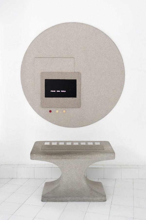 A strange geometric concrete pedestal with 8 buttons below a circular screen.
