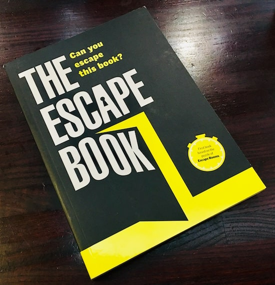 "The Escape Book's black, white, and yellow cover of a door opening. It asks, ""Can you escape this book?"""